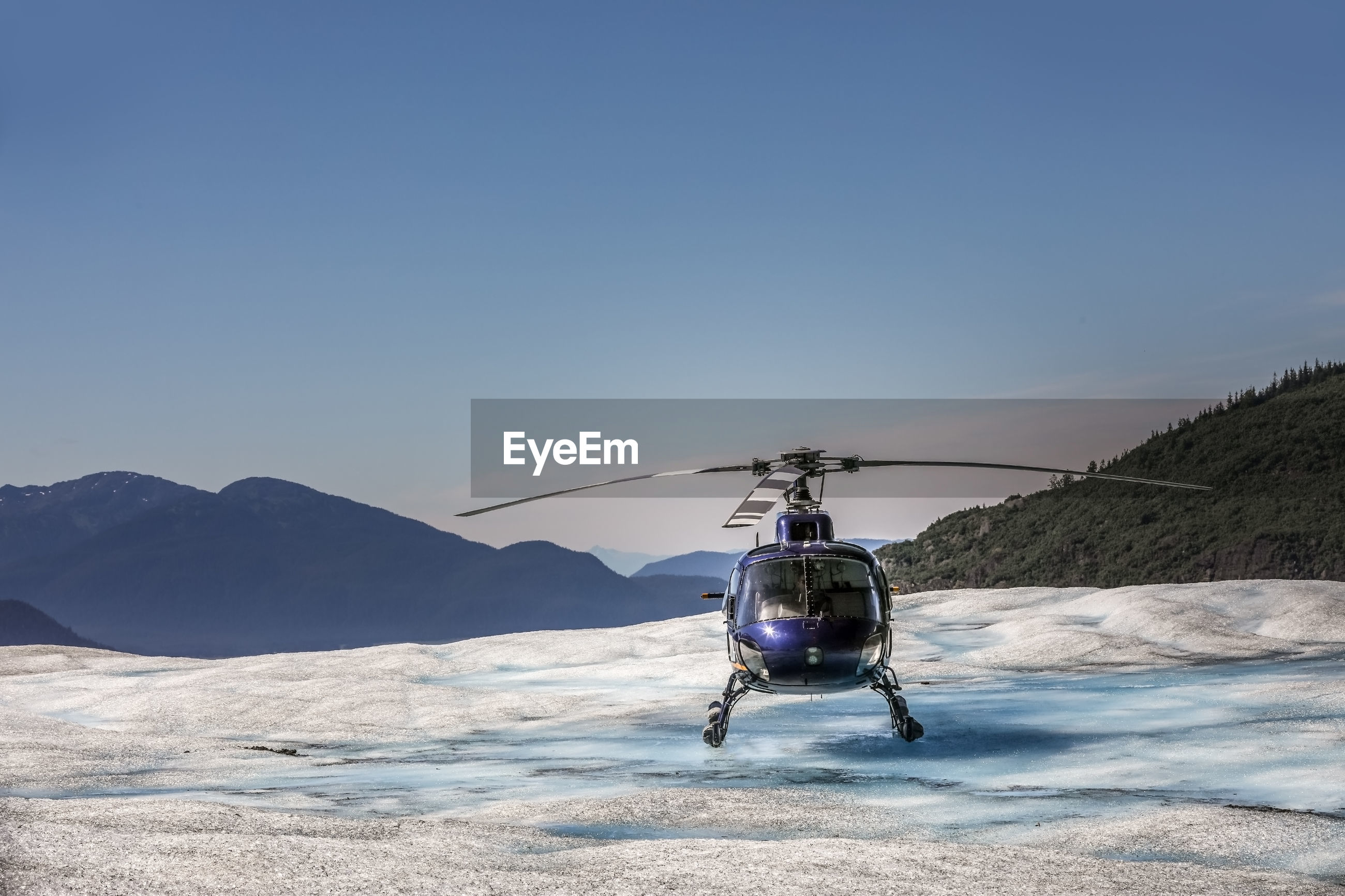 Helicopter landing on snowcapped mountain against sky