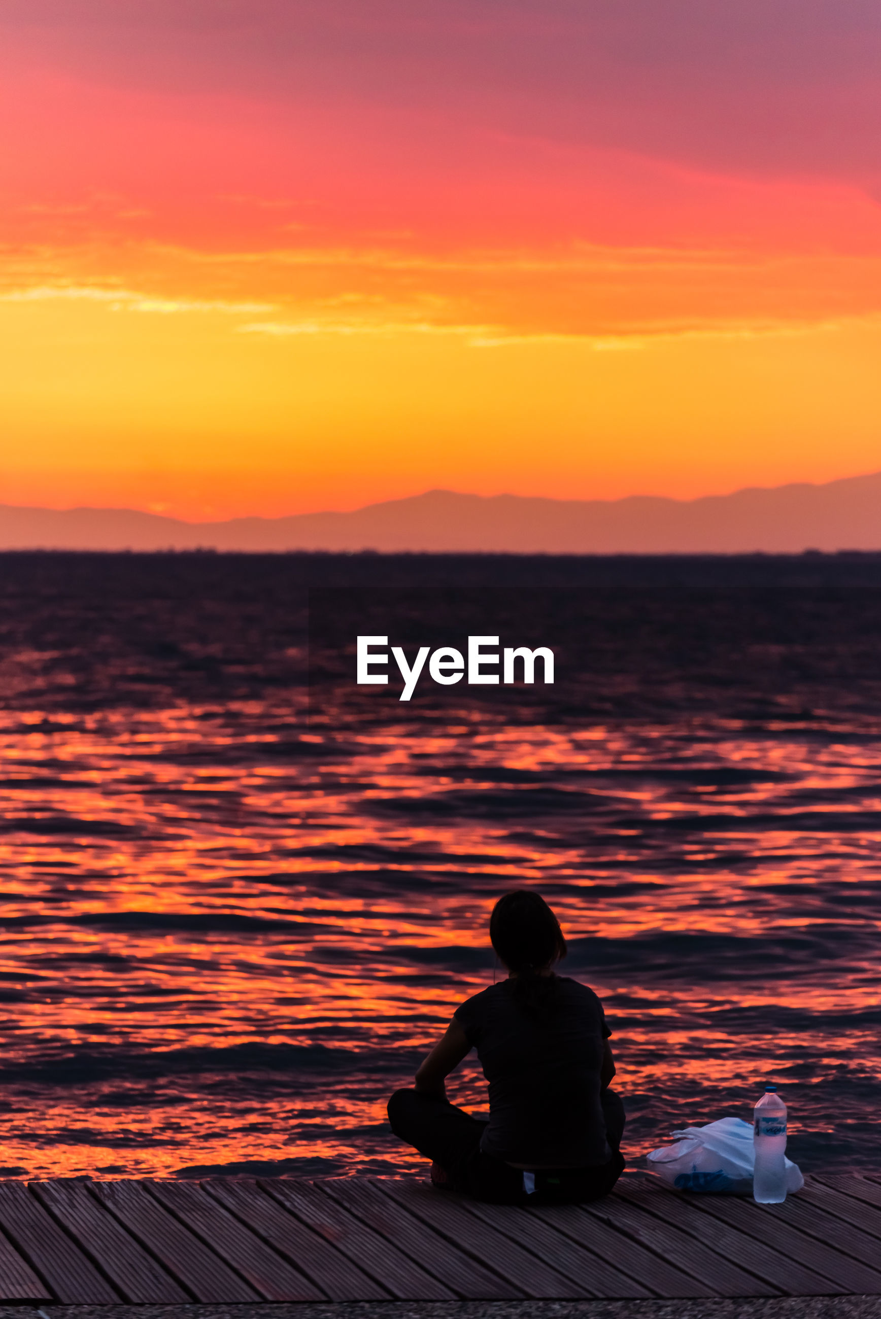 SILHOUETTE MAN SITTING ON SEA AGAINST ORANGE SKY