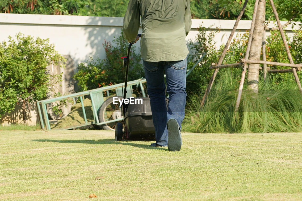 Back portrait gardener pushing the mowing cart on the grass field