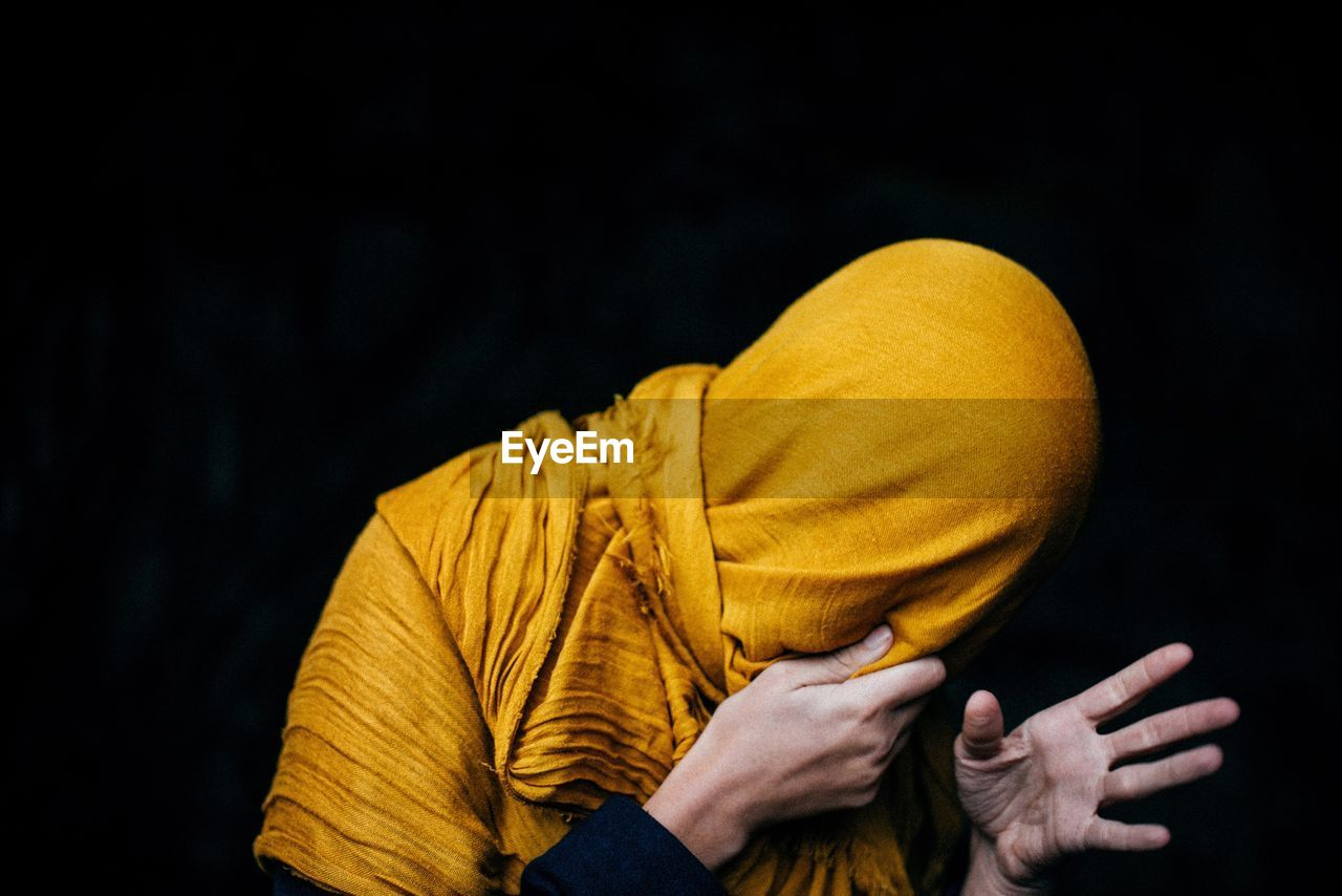 Man wrapped in yellow scarf against black background