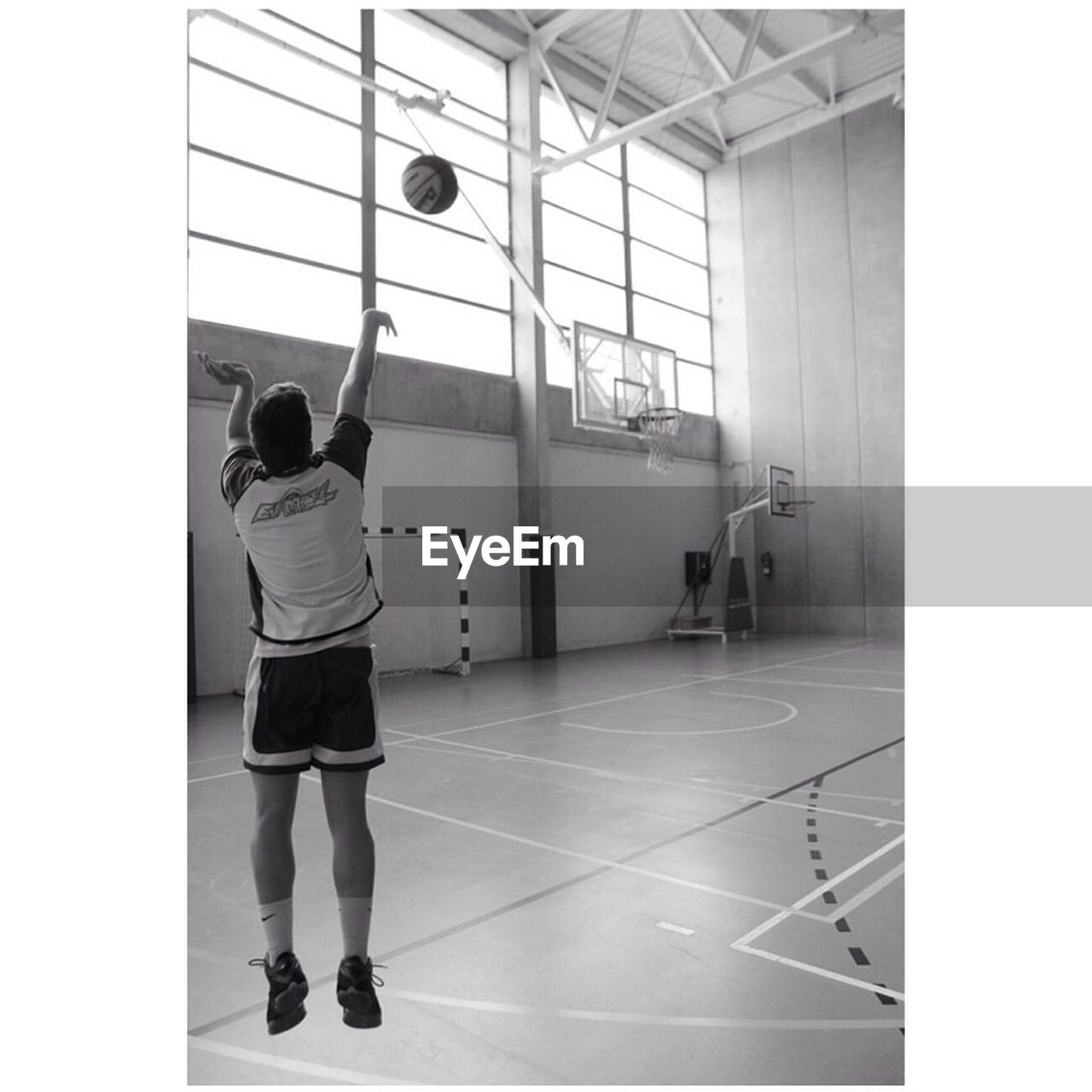 indoors, real people, rear view, full length, one person, gym, lifestyles, exercising, basketball hoop, sport, architecture, day, sports clothing, court, basketball - sport, people
