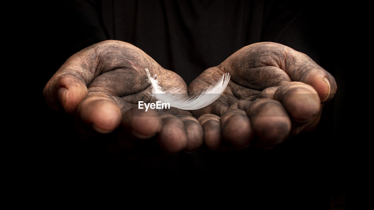 Cropped image of messy hands holding feather against black background