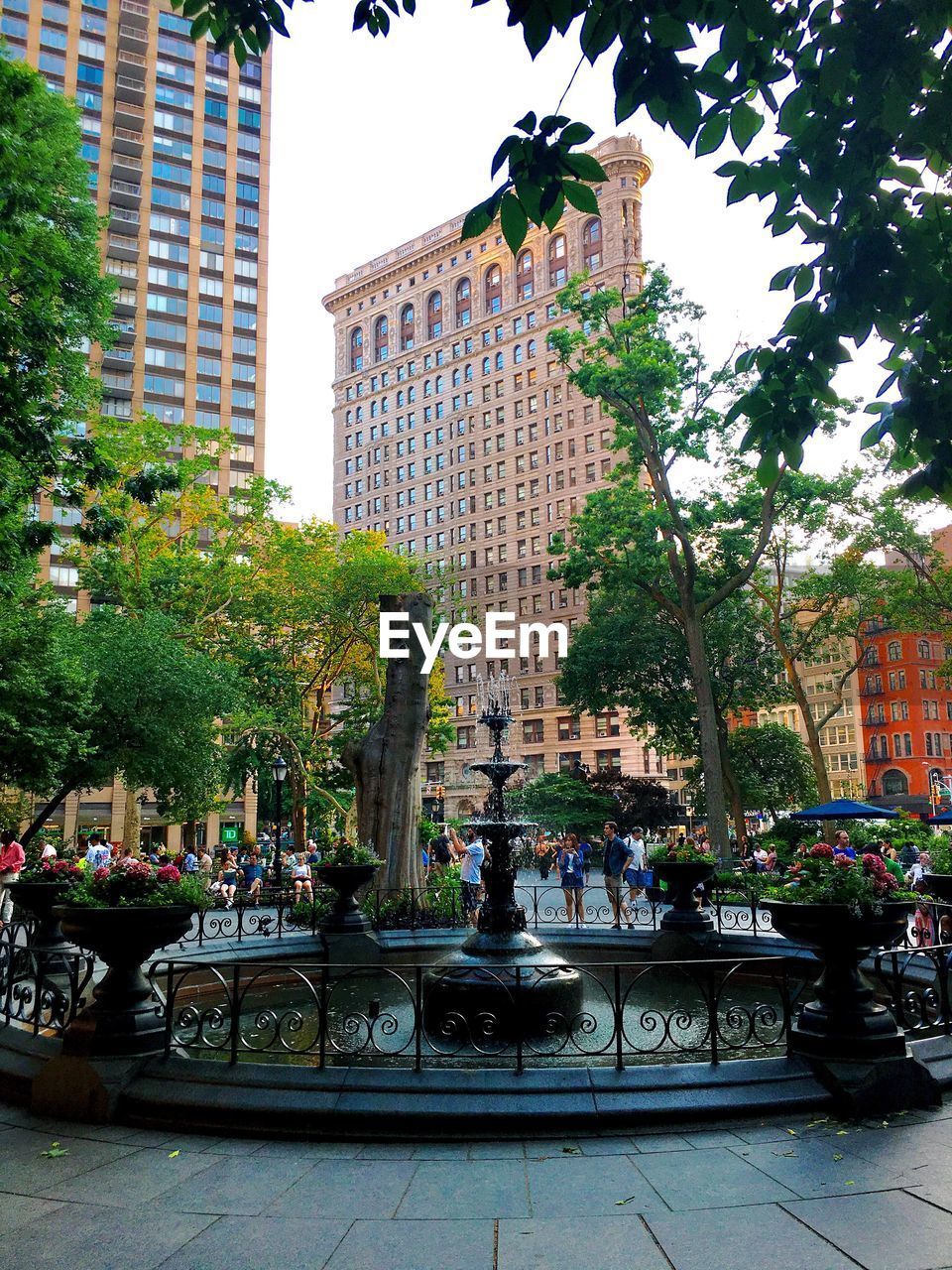 Fountain against buildings and trees in city