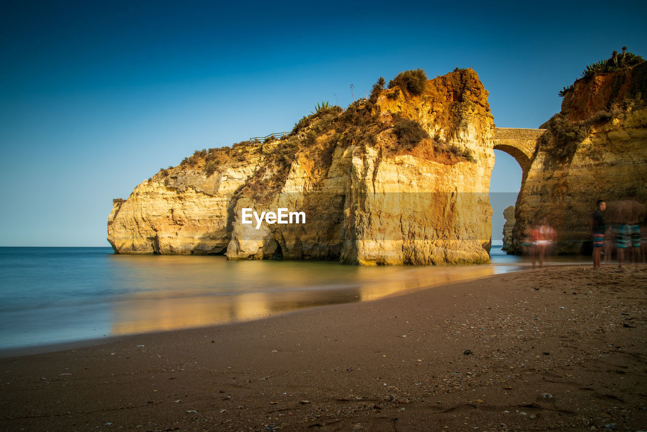 water, sky, sea, land, rock, beauty in nature, beach, rock formation, rock - object, nature, scenics - nature, tranquility, tranquil scene, clear sky, solid, sand, arch, incidental people, blue, natural arch, outdoors, eroded