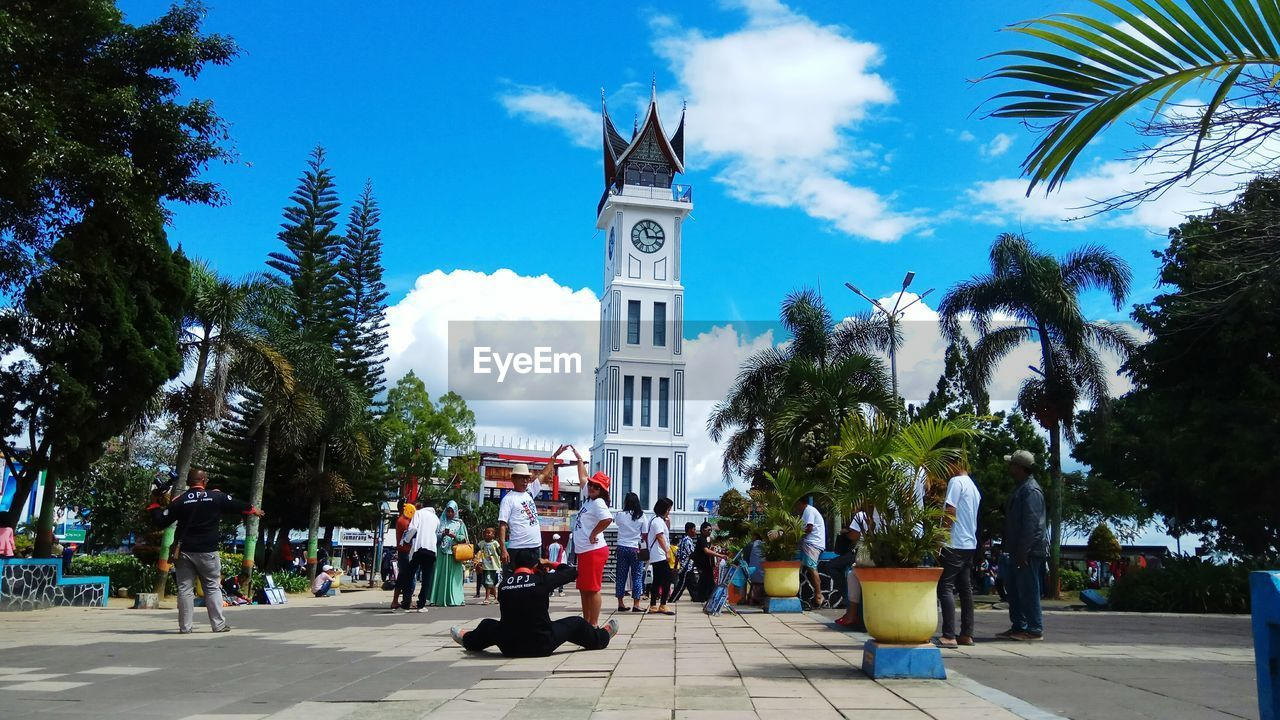 tree, plant, architecture, sky, group of people, built structure, building exterior, nature, palm tree, building, real people, tropical climate, city, tower, men, crowd, people, day, women, outdoors