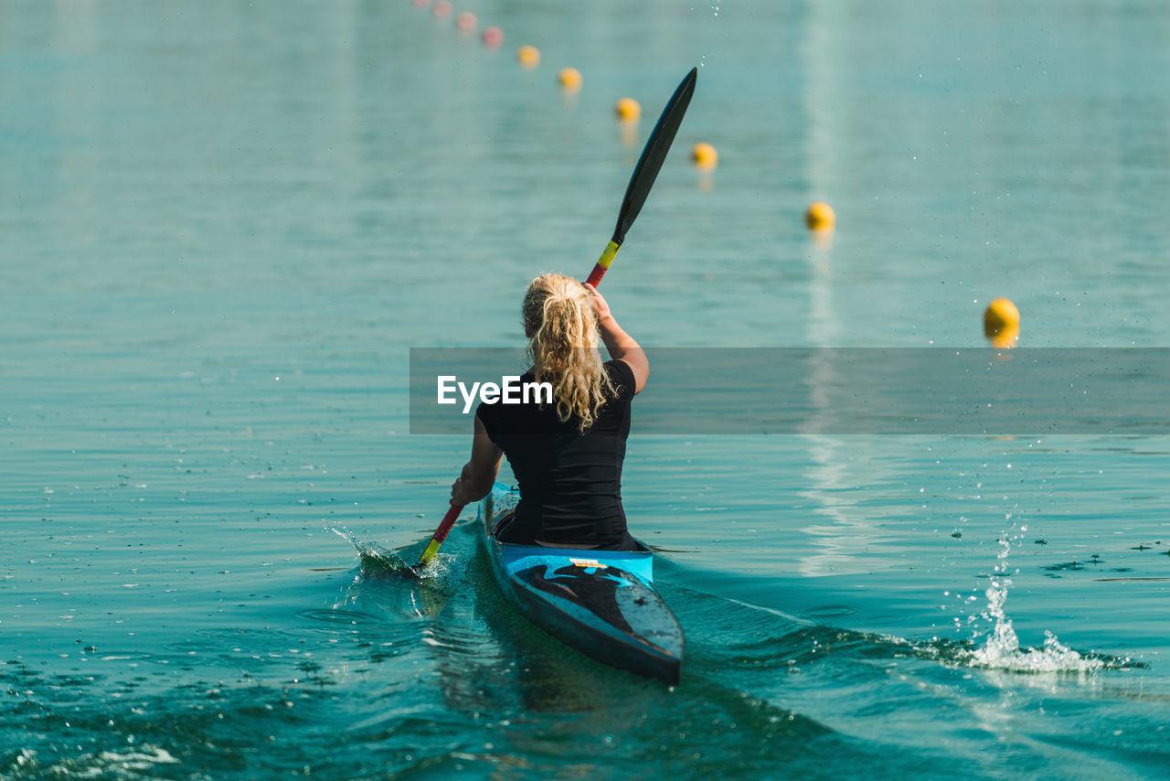 Rear View Of Woman Kayaking In Lake