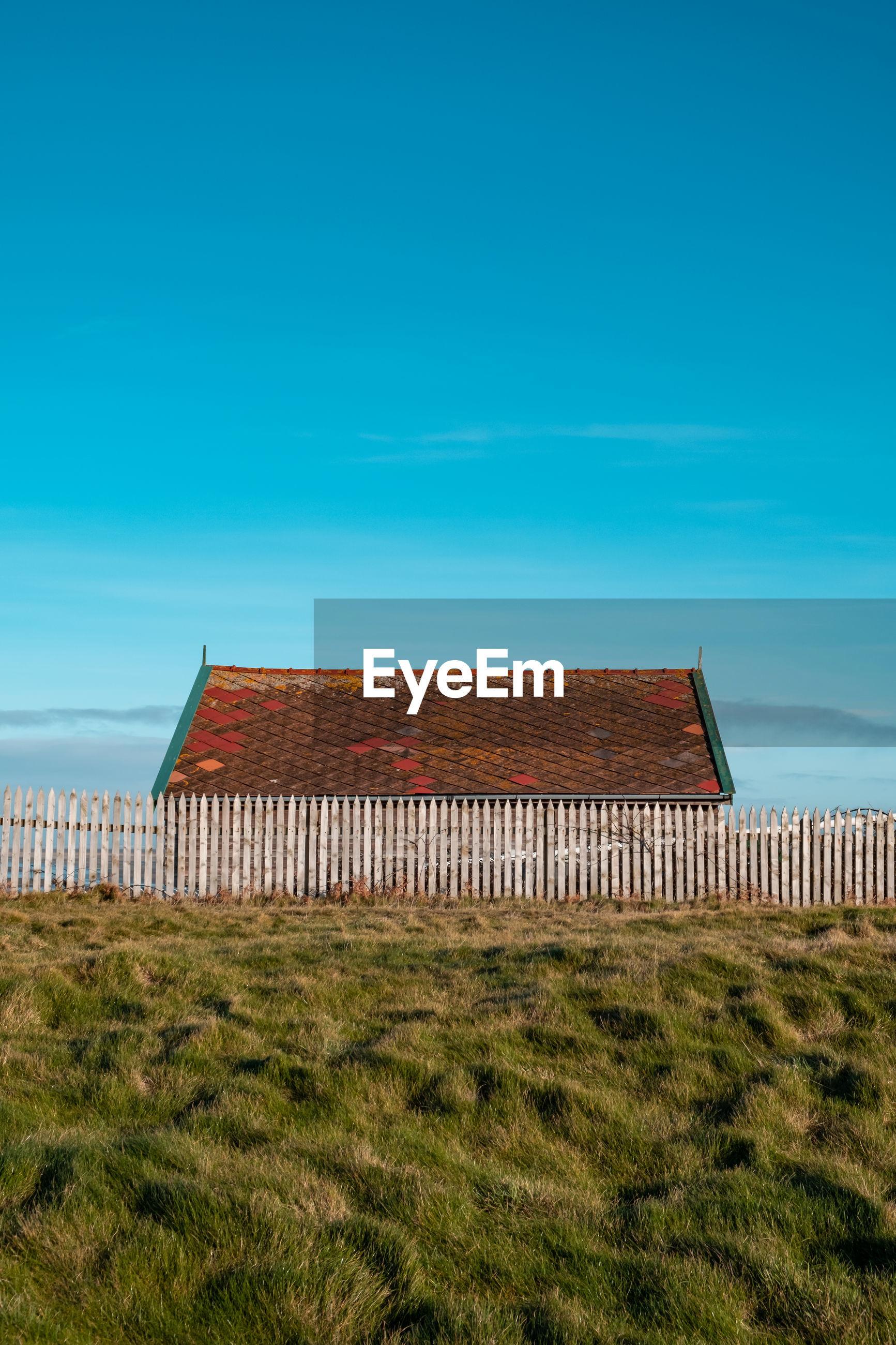 HOUSES ON FIELD AGAINST BLUE SKY