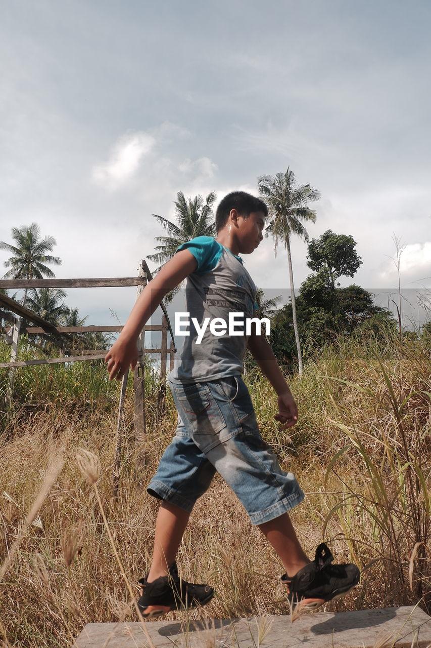 FULL LENGTH OF BOY ON FIELD
