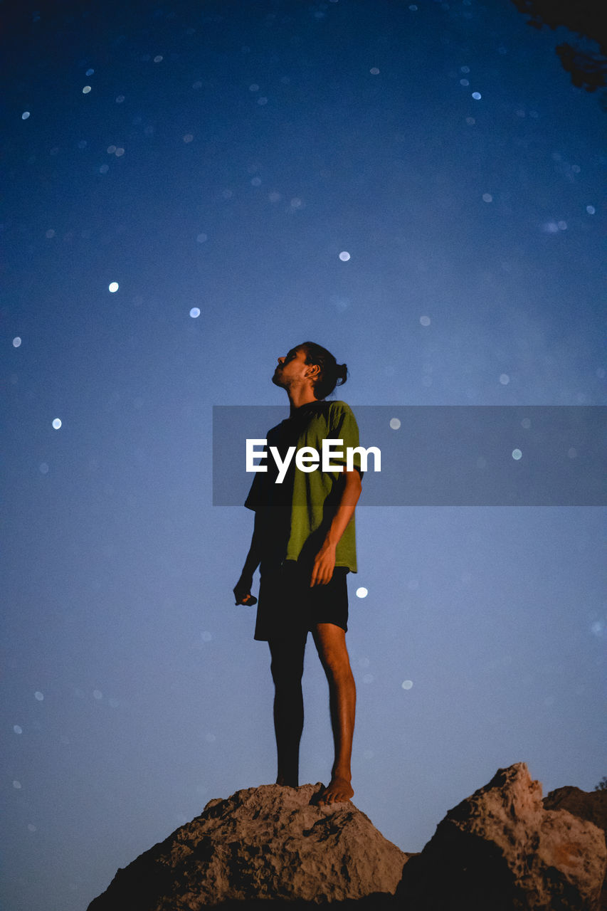 Low angle view of man standing on rock against night sky