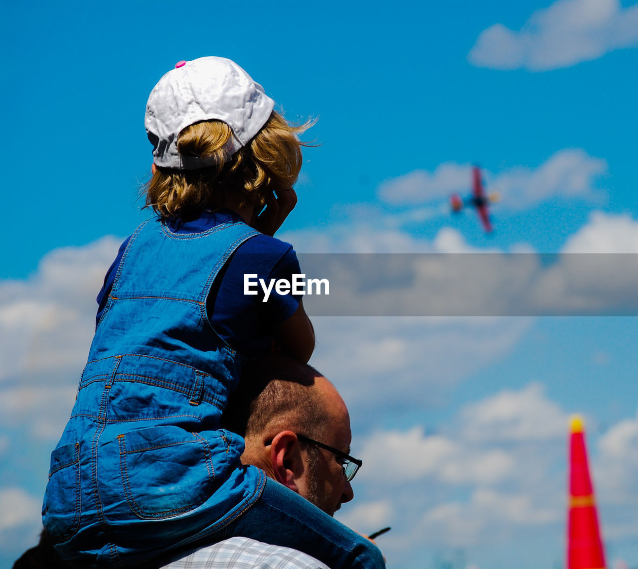 Rear view of daughter sitting on father shoulders against sky
