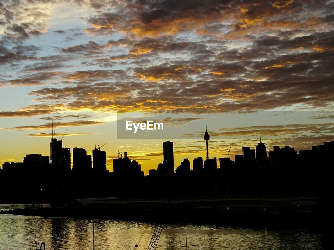 architecture, sunset, building exterior, skyscraper, built structure, city, sky, cloud - sky, waterfront, travel destinations, river, water, cityscape, silhouette, urban skyline, modern, no people, outdoors, growth, sunlight, nature, day