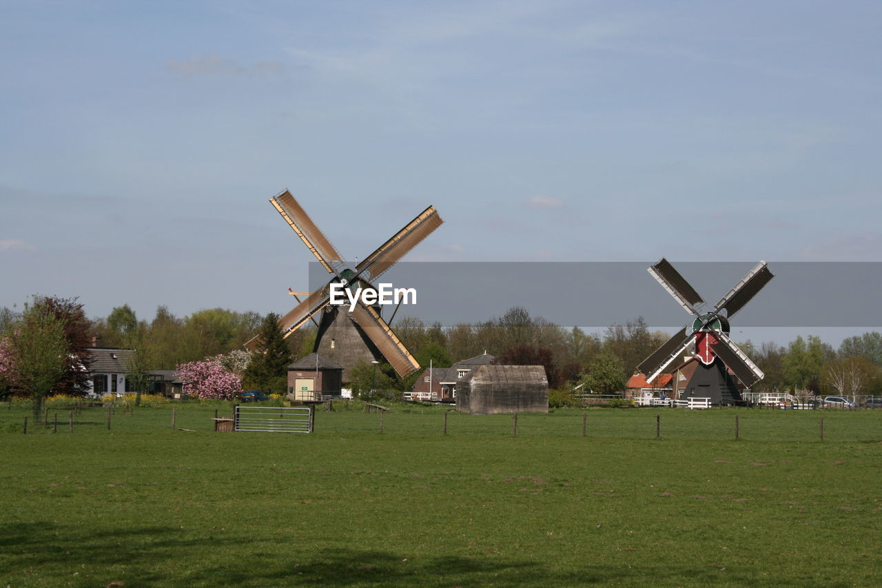 sky, alternative energy, renewable energy, environment, plant, fuel and power generation, wind turbine, wind power, nature, turbine, grass, field, landscape, environmental conservation, traditional windmill, land, architecture, building exterior, day, built structure, no people, outdoors
