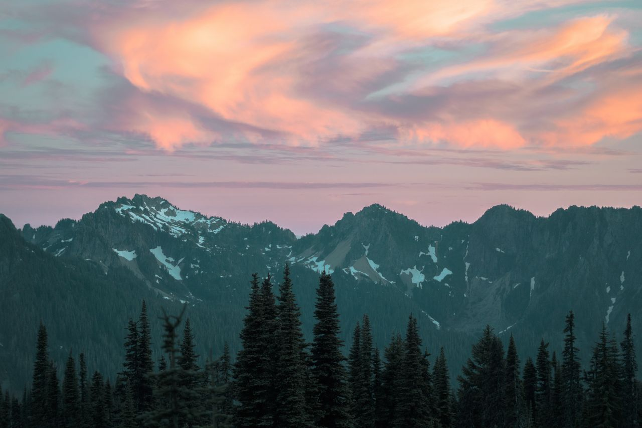 Scenic view of mountains and trees on against sky at sunset