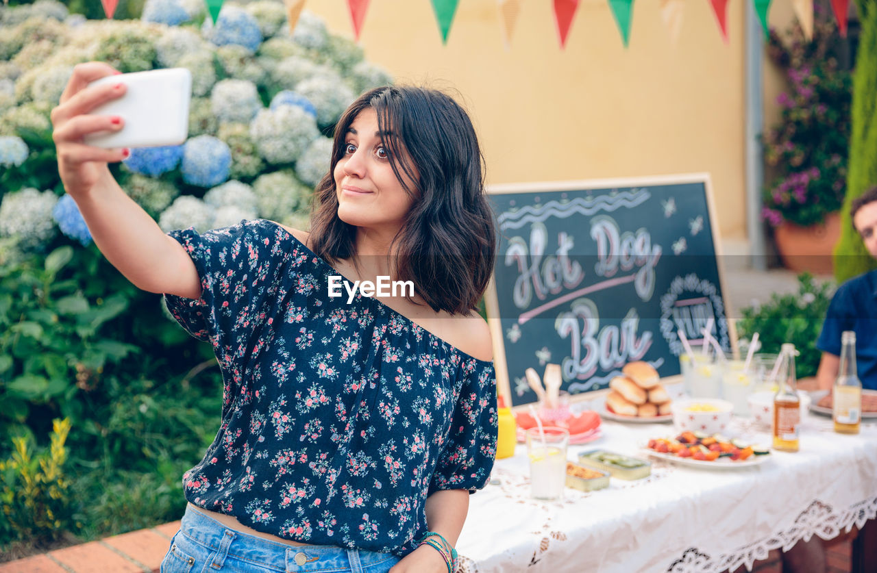 Young Woman Taking Selfie While Standing By Food Stall