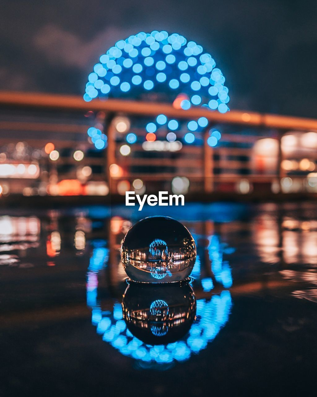 illuminated, night, city, reflection, focus on foreground, water, architecture, built structure, glowing, nature, geometric shape, circle, outdoors, shape, transportation, building exterior, no people, motion, waterfront