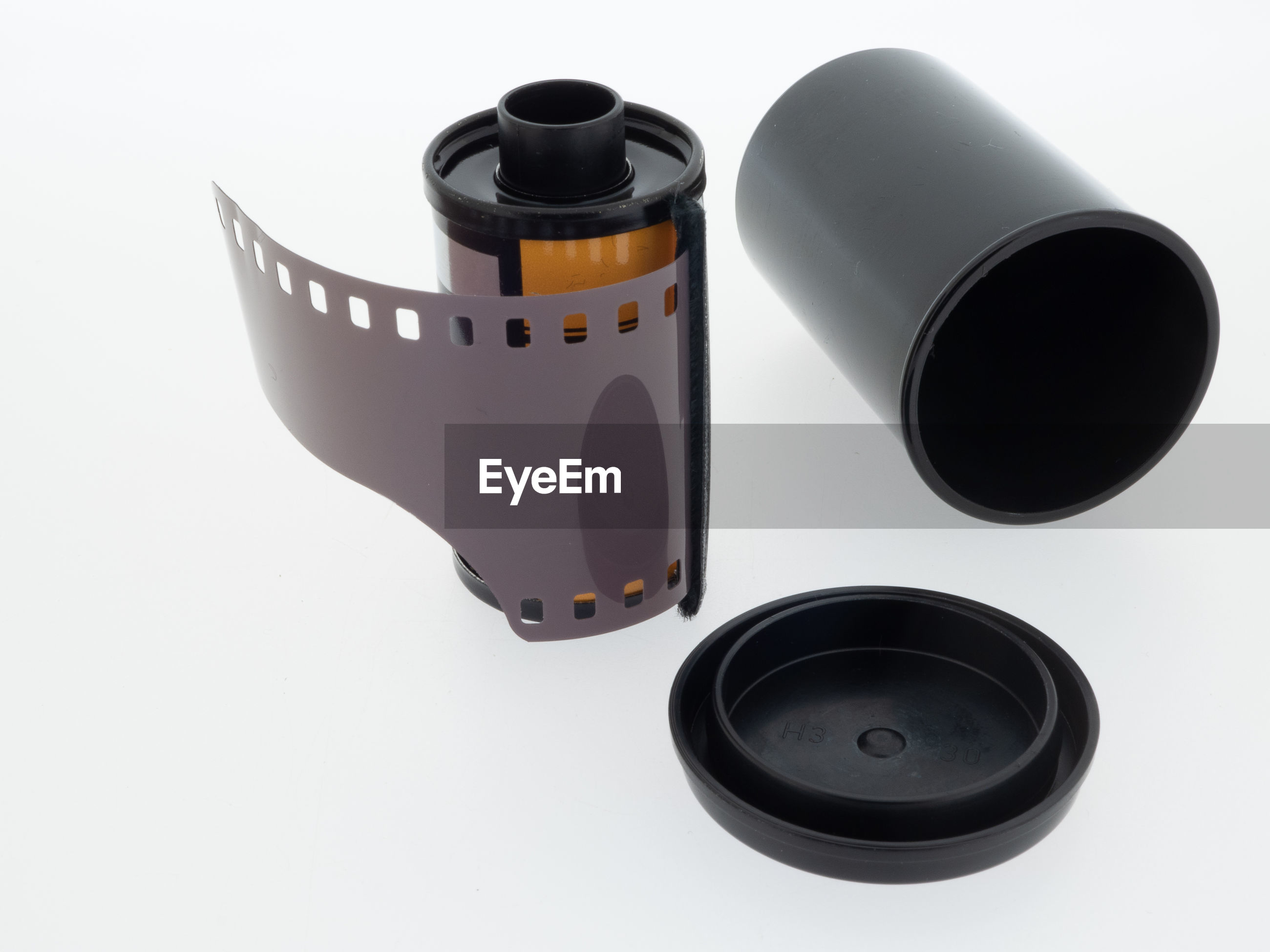 Close-up of film reel by container against white background