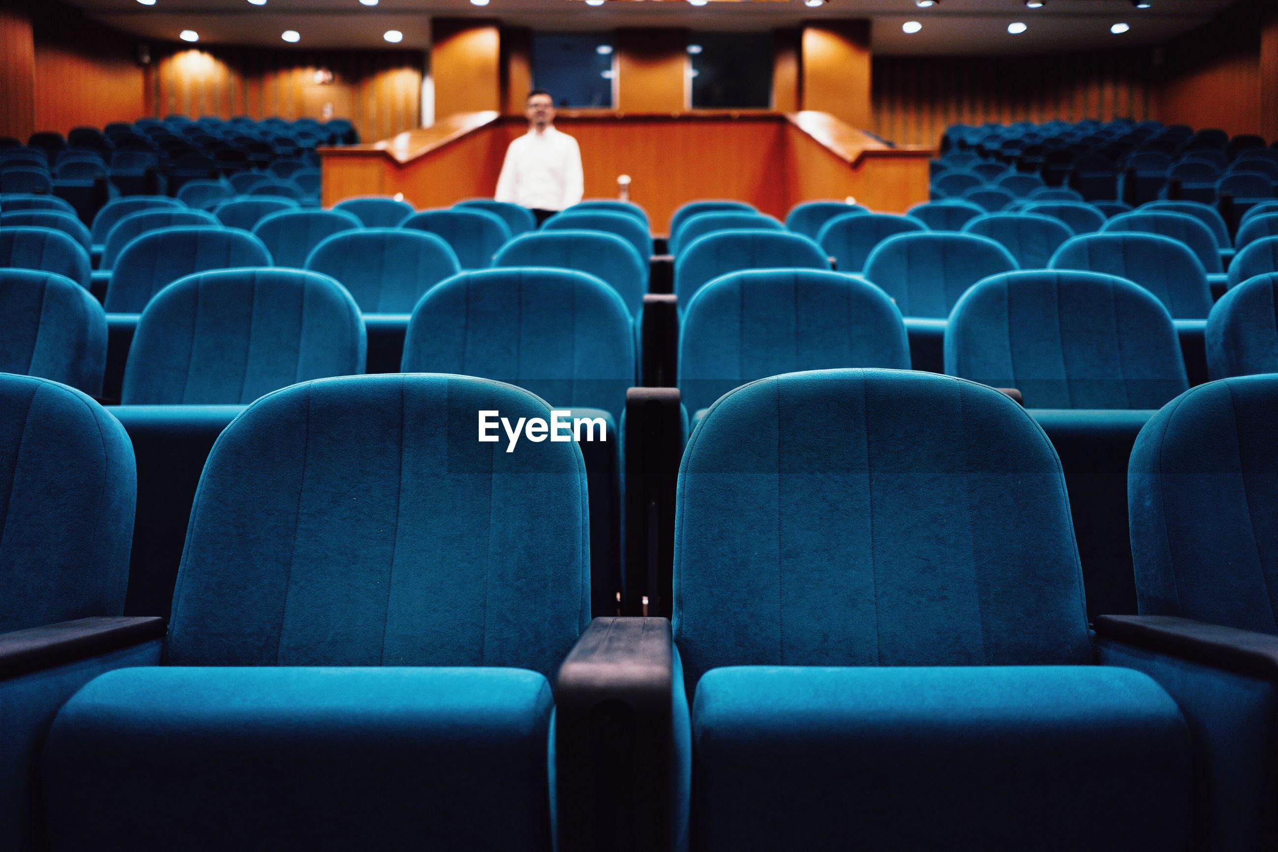 Defocused mid adult man standing amidst blue empty chairs in auditorium