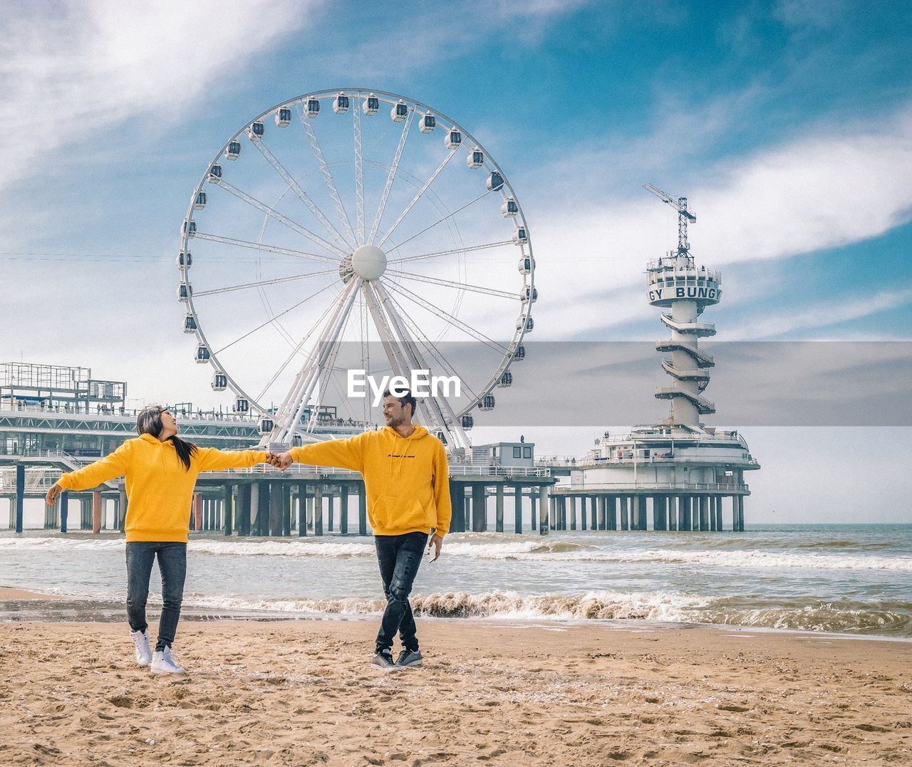 sky, water, amusement park ride, cloud - sky, ferris wheel, leisure activity, sea, nature, full length, amusement park, architecture, built structure, men, beach, real people, tourism, arts culture and entertainment, day, travel destinations, outdoors