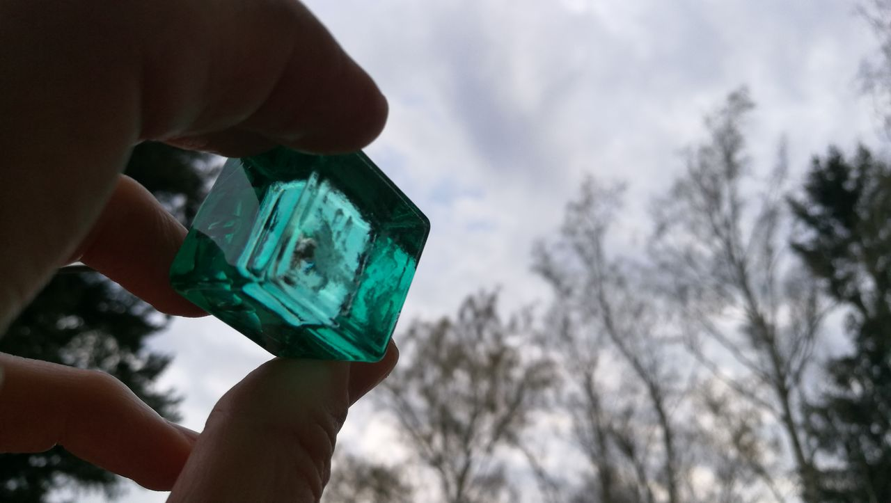 Cropped Hand Holding Blue Glass Block By Trees Against Cloudy Sky