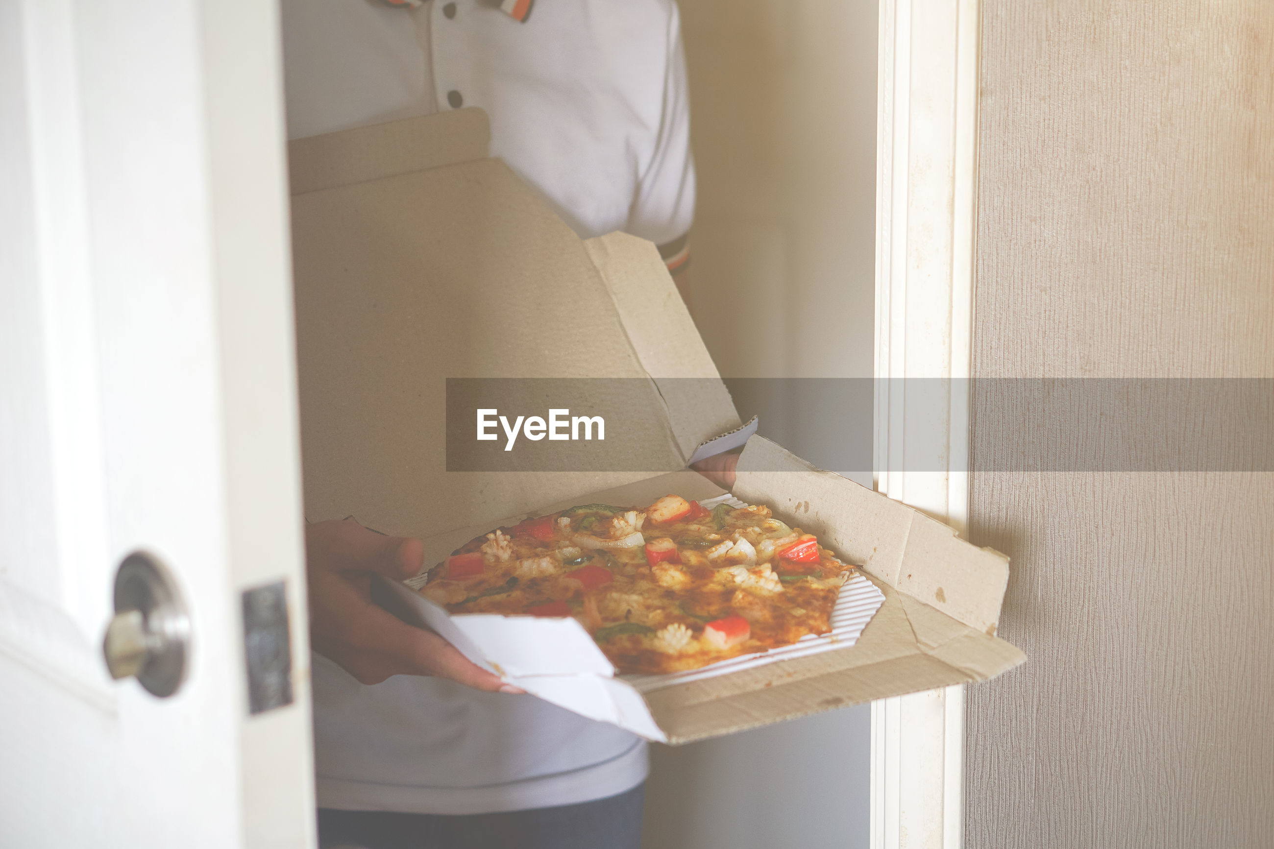 Midsection of man holding pizza box at home