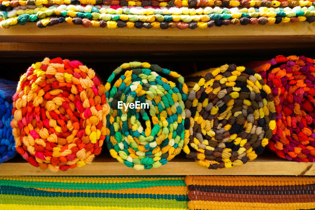 Close-up of colorful rolled fabric in shelf