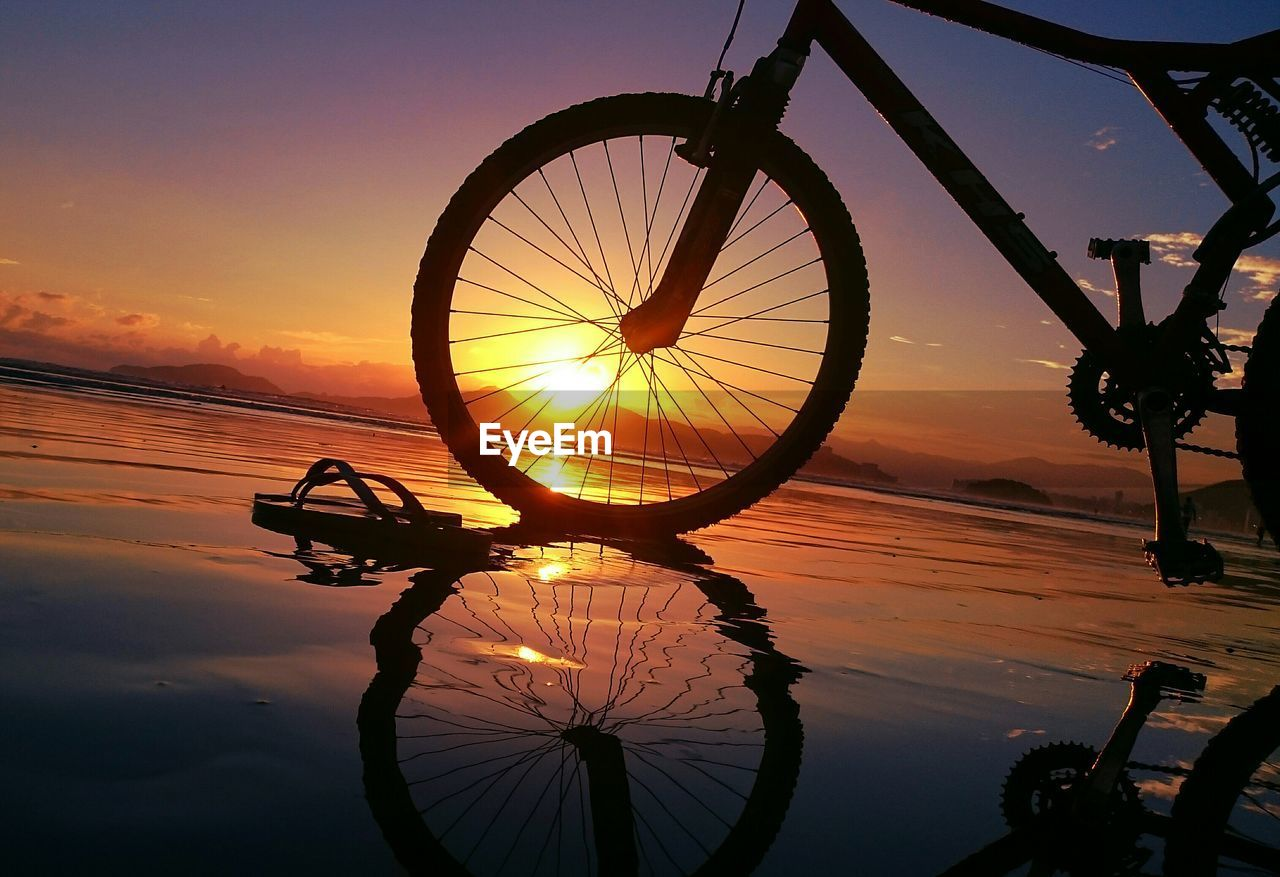 sunset, bicycle, reflection, mode of transport, silhouette, orange color, sky, transportation, sun, nature, wheel, water, outdoors, scenics, cloud - sky, land vehicle, stationary, beauty in nature, spoke, no people, close-up