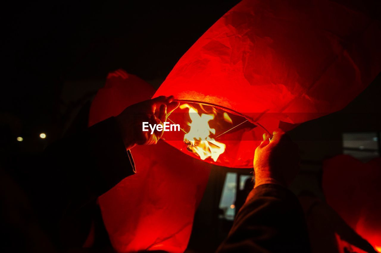burning, real people, fire, men, flame, night, fire - natural phenomenon, human body part, illuminated, heat - temperature, people, human hand, holding, hand, unrecognizable person, lifestyles, two people, body part, leisure activity, dark, paper lantern