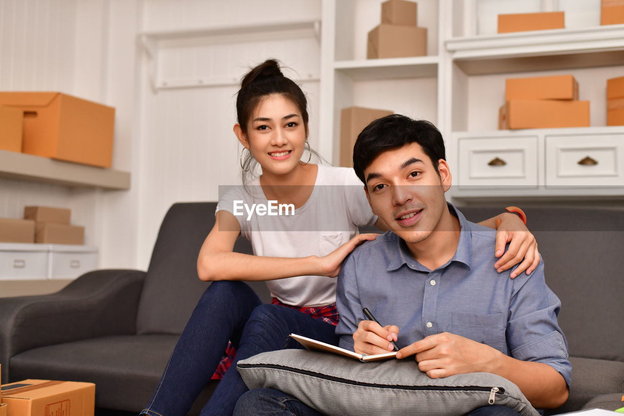 sitting, young adult, two people, togetherness, young men, front view, young women, smiling, lifestyles, sofa, indoors, home interior, emotion, looking at camera, casual clothing, portrait, men, three quarter length, furniture, happiness, couple - relationship, living room, wireless technology