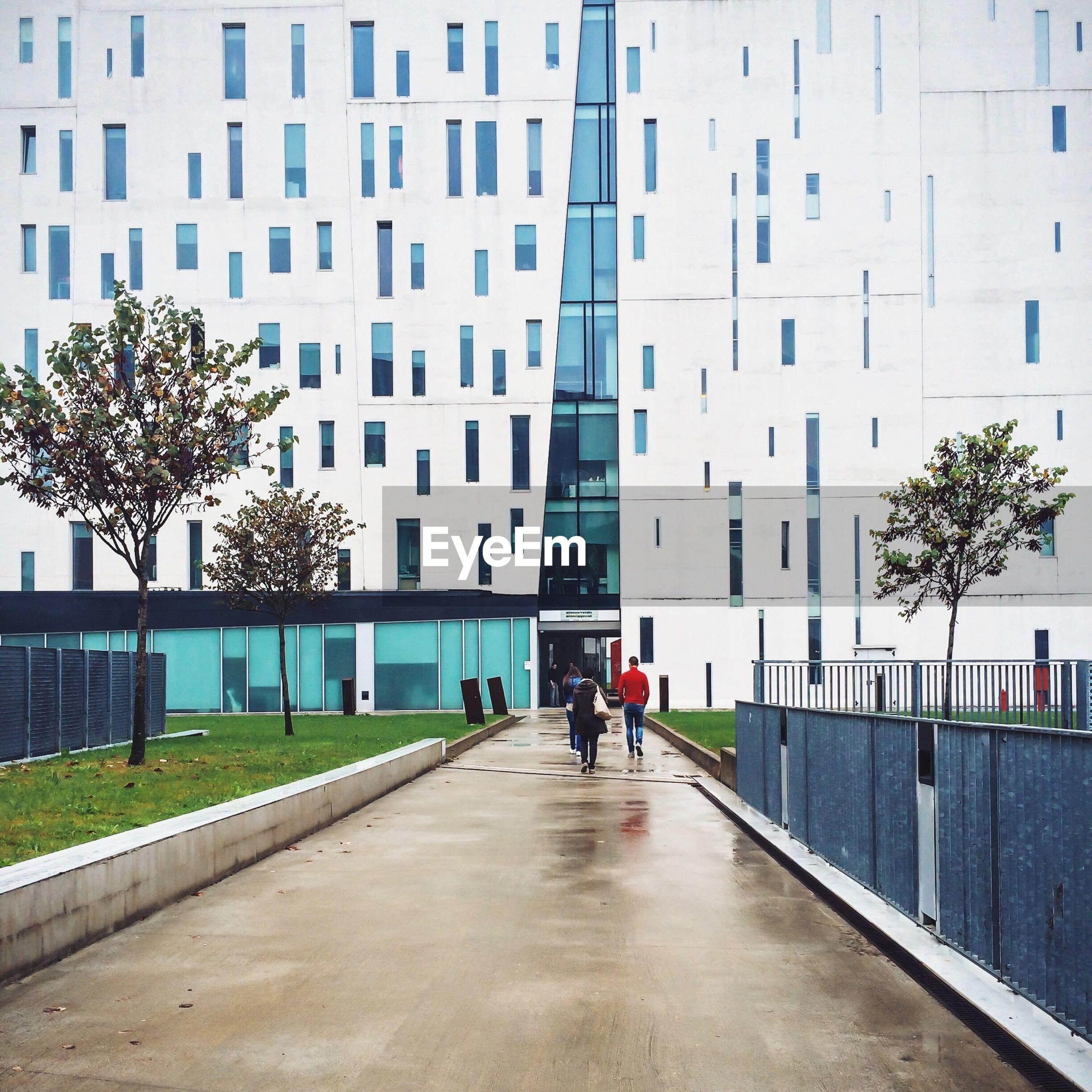 Rear view of people walking in pathway against building