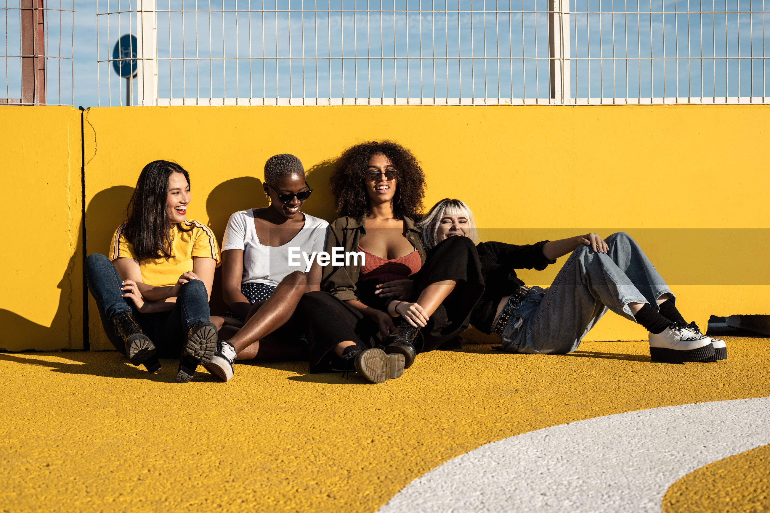 GROUP OF PEOPLE SITTING ON YELLOW SEAT