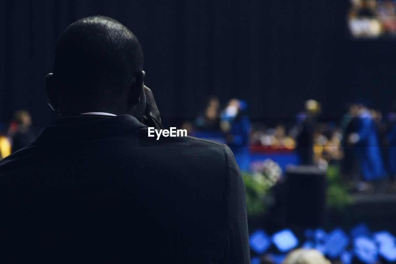 Rear View Of Man At Graduation Ceremony In School Building