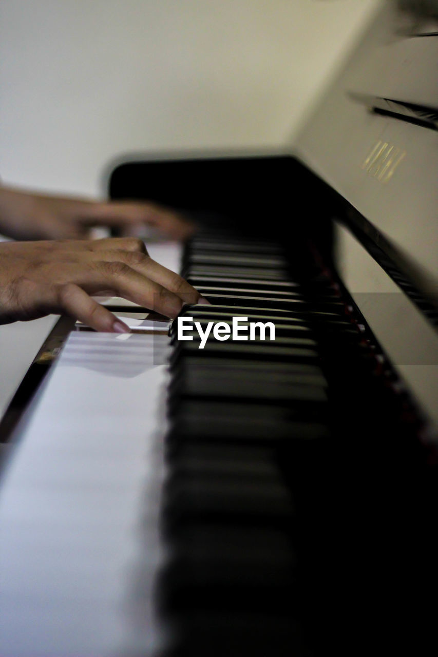 musical equipment, musical instrument, music, human hand, piano, hand, arts culture and entertainment, selective focus, piano key, playing, human body part, one person, indoors, real people, human finger, finger, musician, pianist, body part, keyboard, keyboard instrument
