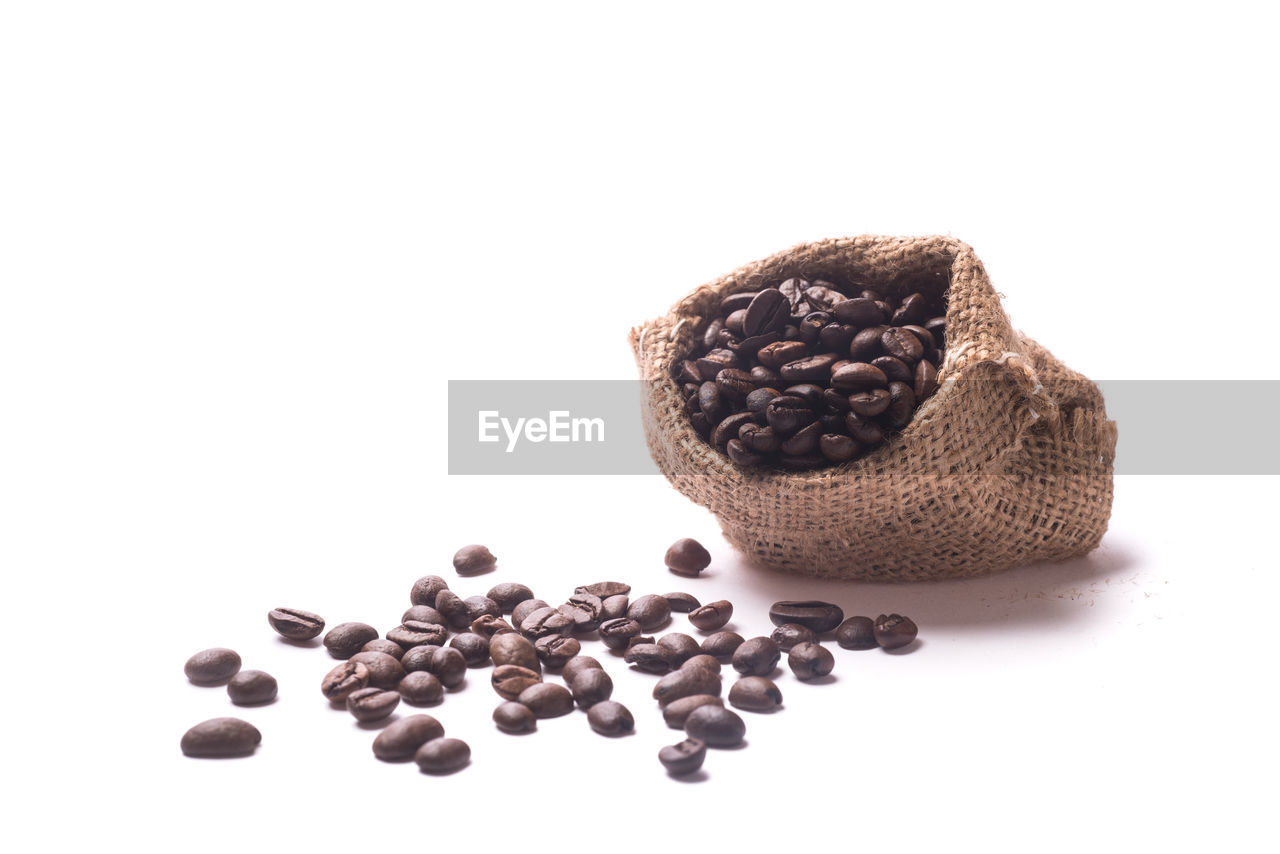 Coffee beans spilling from burlap sack against white background