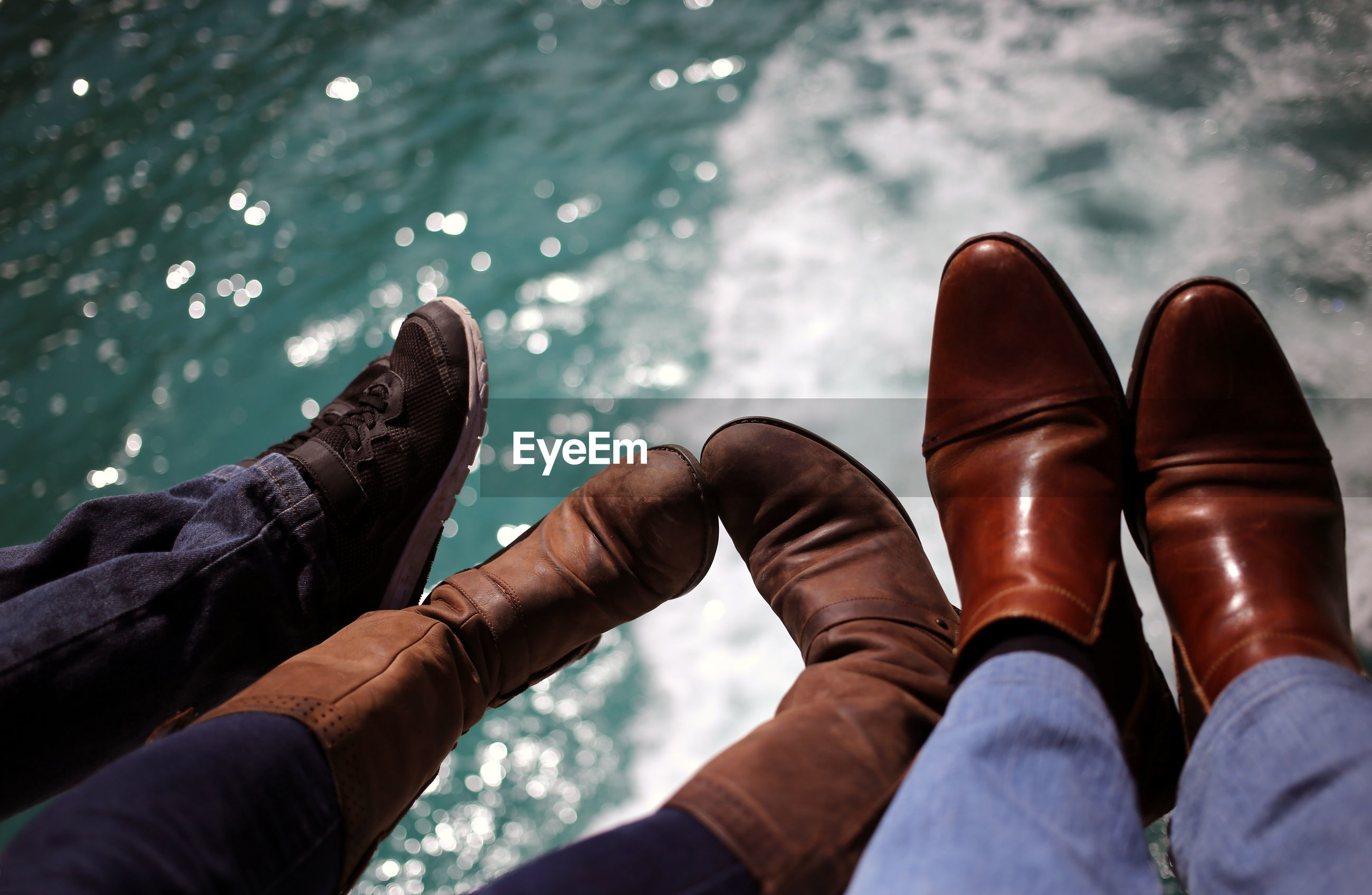 Low section of family wearing shoes over sea