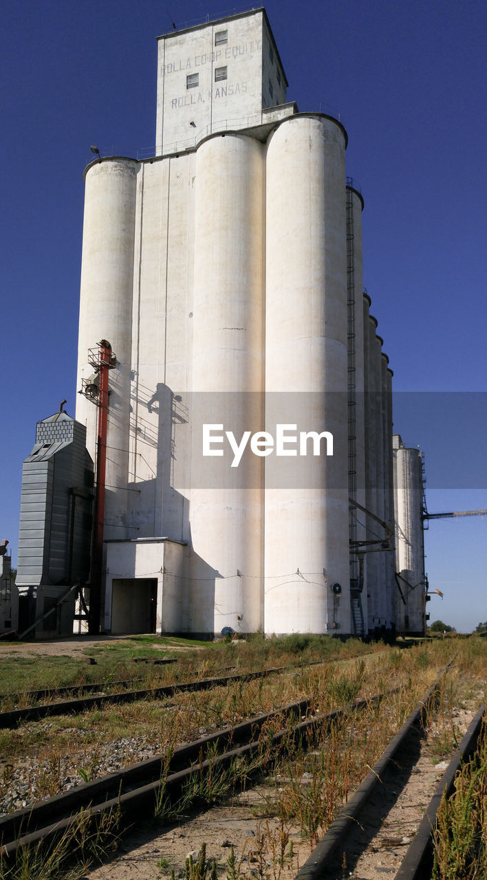 factory, sky, architecture, industry, built structure, building exterior, silo, no people, clear sky, nature, day, fuel and power generation, storage tank, low angle view, storage compartment, outdoors, agriculture, industrial building, blue, sunlight, cooling tower, pollution
