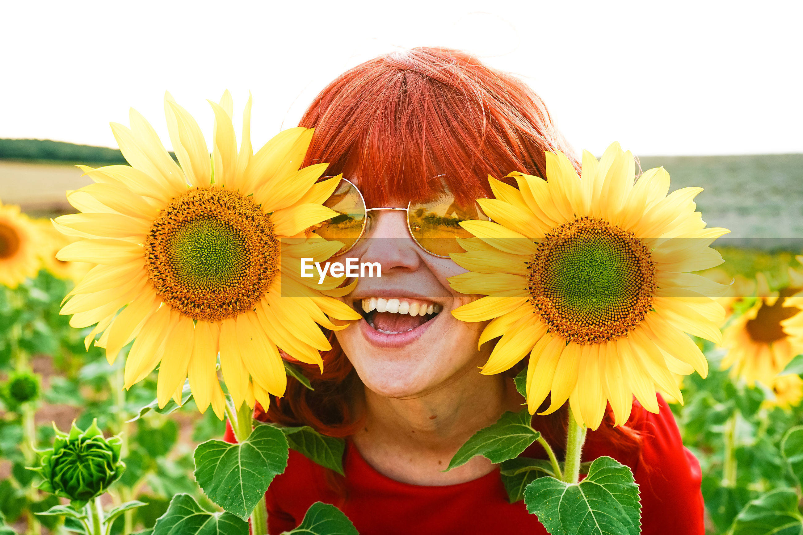 CLOSE-UP PORTRAIT OF SMILING WOMAN AGAINST YELLOW SUNFLOWER