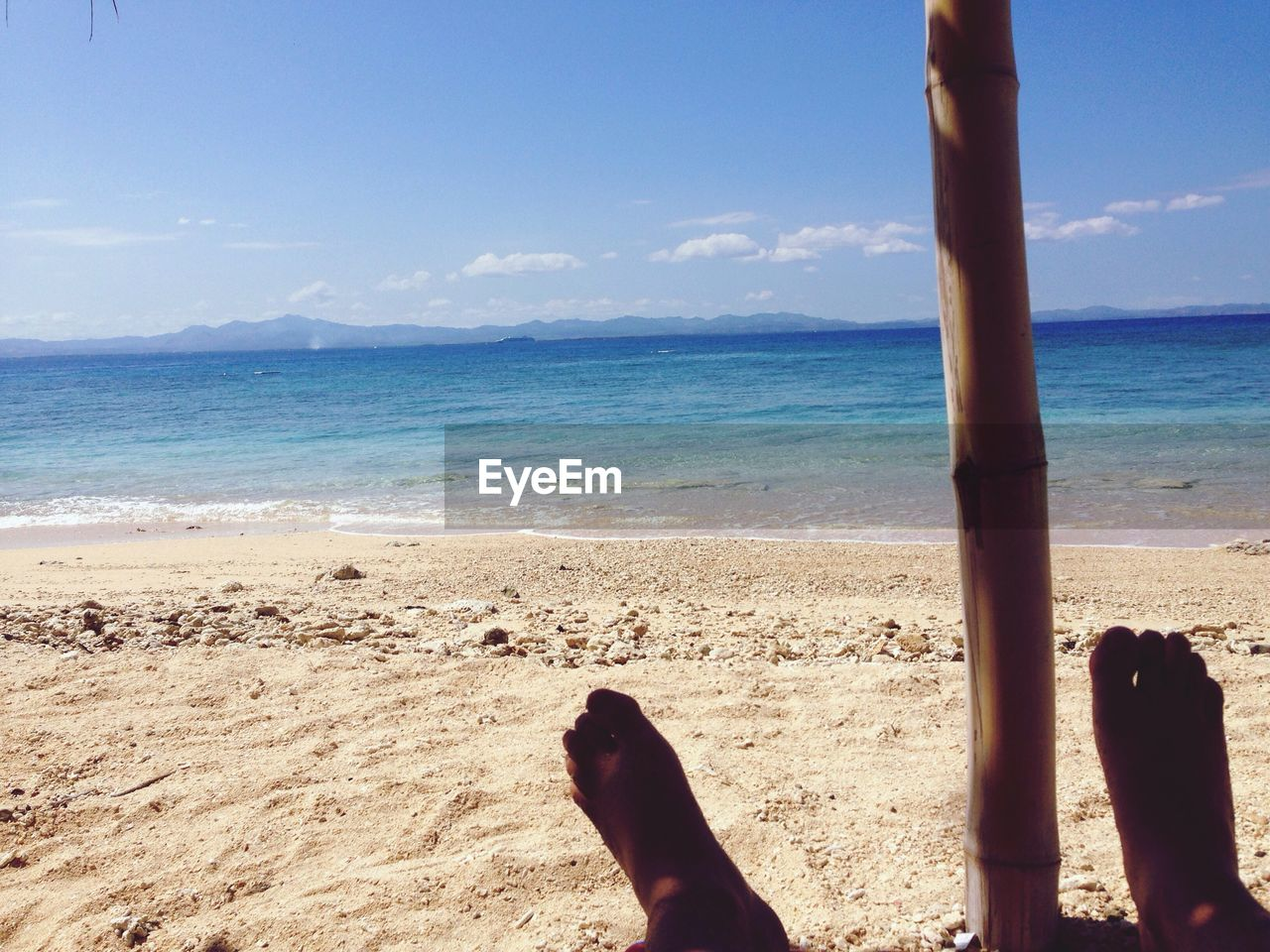 sea, beach, land, water, sky, low section, human leg, human body part, body part, nature, horizon, horizon over water, barefoot, real people, sand, beauty in nature, scenics - nature, one person, relaxation, human foot, outdoors, human limb