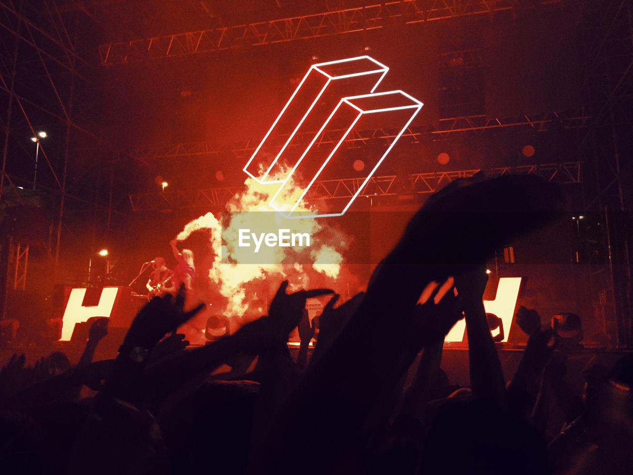 silhouette, real people, group of people, night, men, people, indoors, lifestyles, arts culture and entertainment, illuminated, leisure activity, performance, crowd, communication, human hand, fire, burning, sitting, fire - natural phenomenon, stage