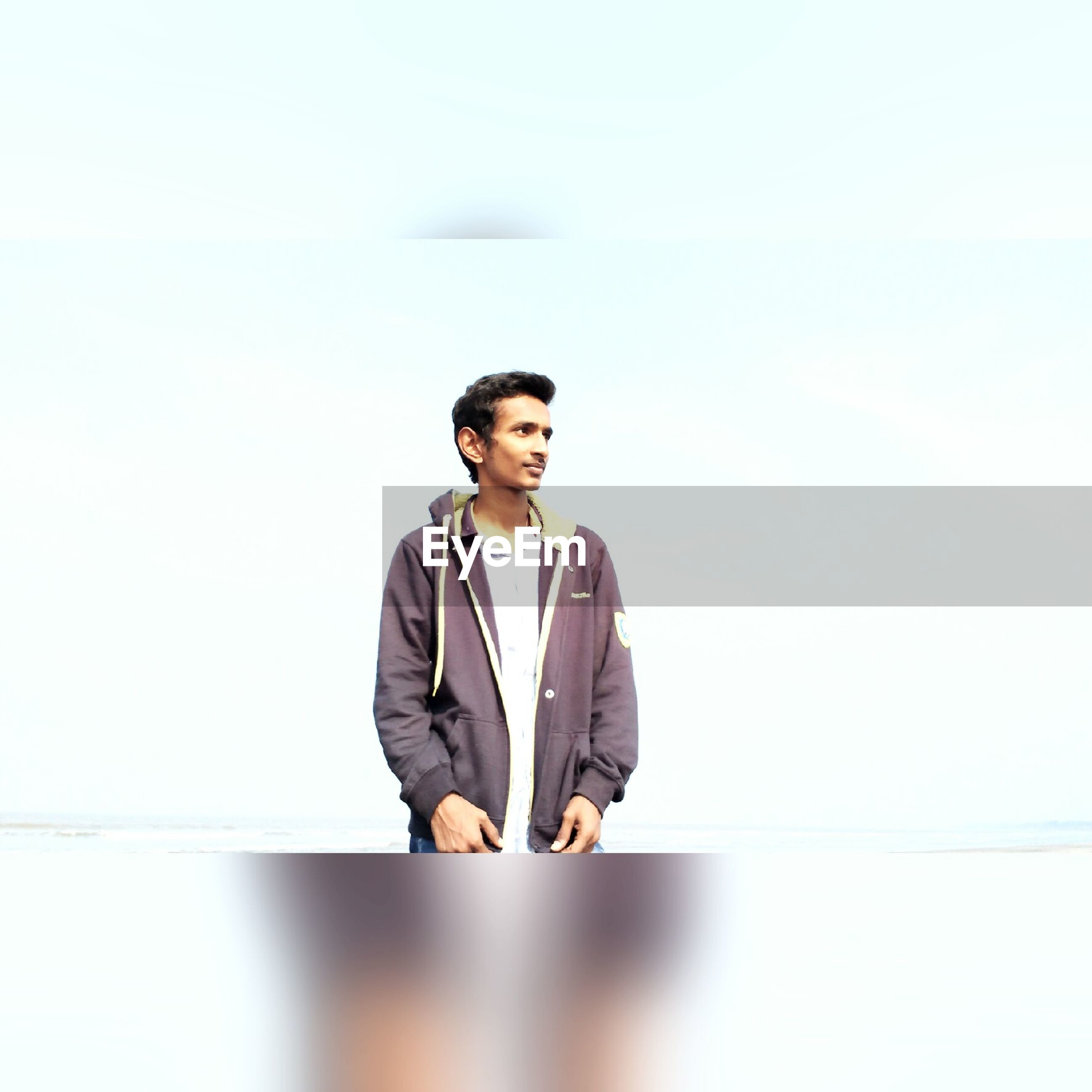 casual clothing, lifestyles, young adult, young men, person, portrait, standing, looking at camera, copy space, front view, leisure activity, waist up, three quarter length, smiling, clear sky, happiness, holding
