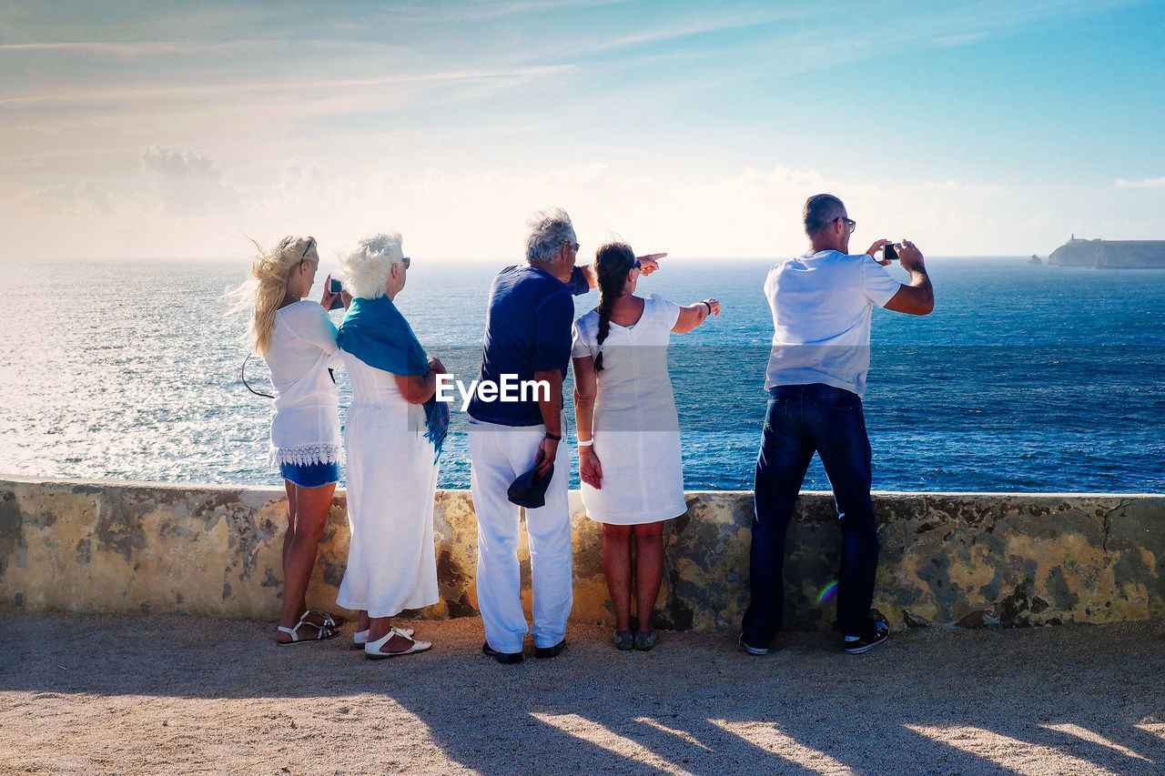 Rear View Of People Standing On Footpath While Pointing At Sea