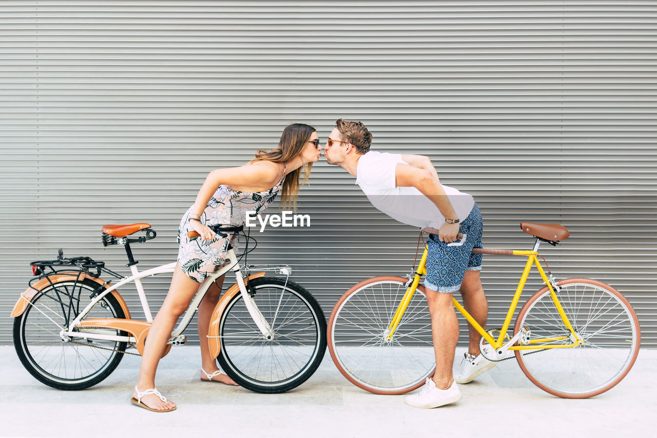 Side View Of Couple With Bicycles Kissing Outdoors