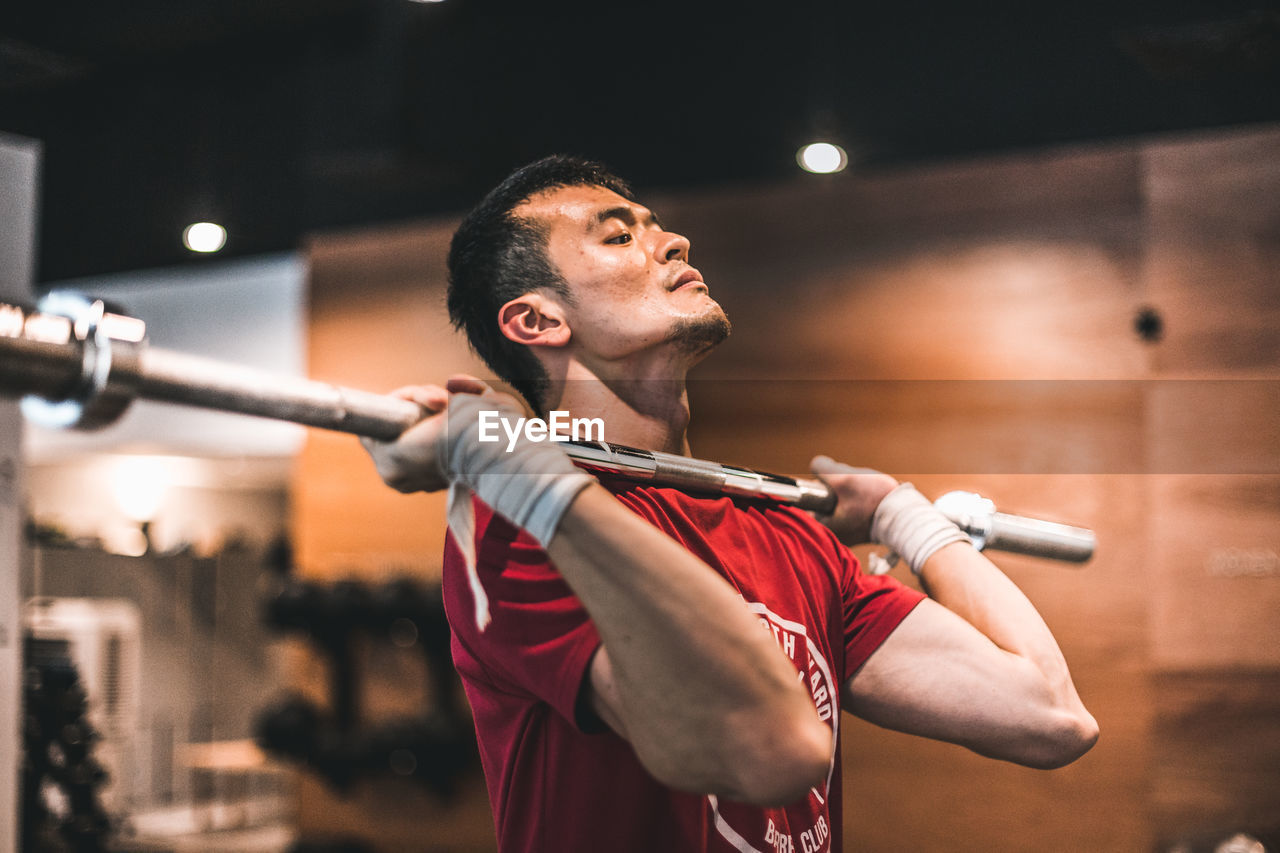 one person, focus on foreground, real people, waist up, men, young men, young adult, arts culture and entertainment, performance, holding, indoors, standing, lifestyles, sport, looking away, front view, leisure activity, skill, sword, arms raised, stage