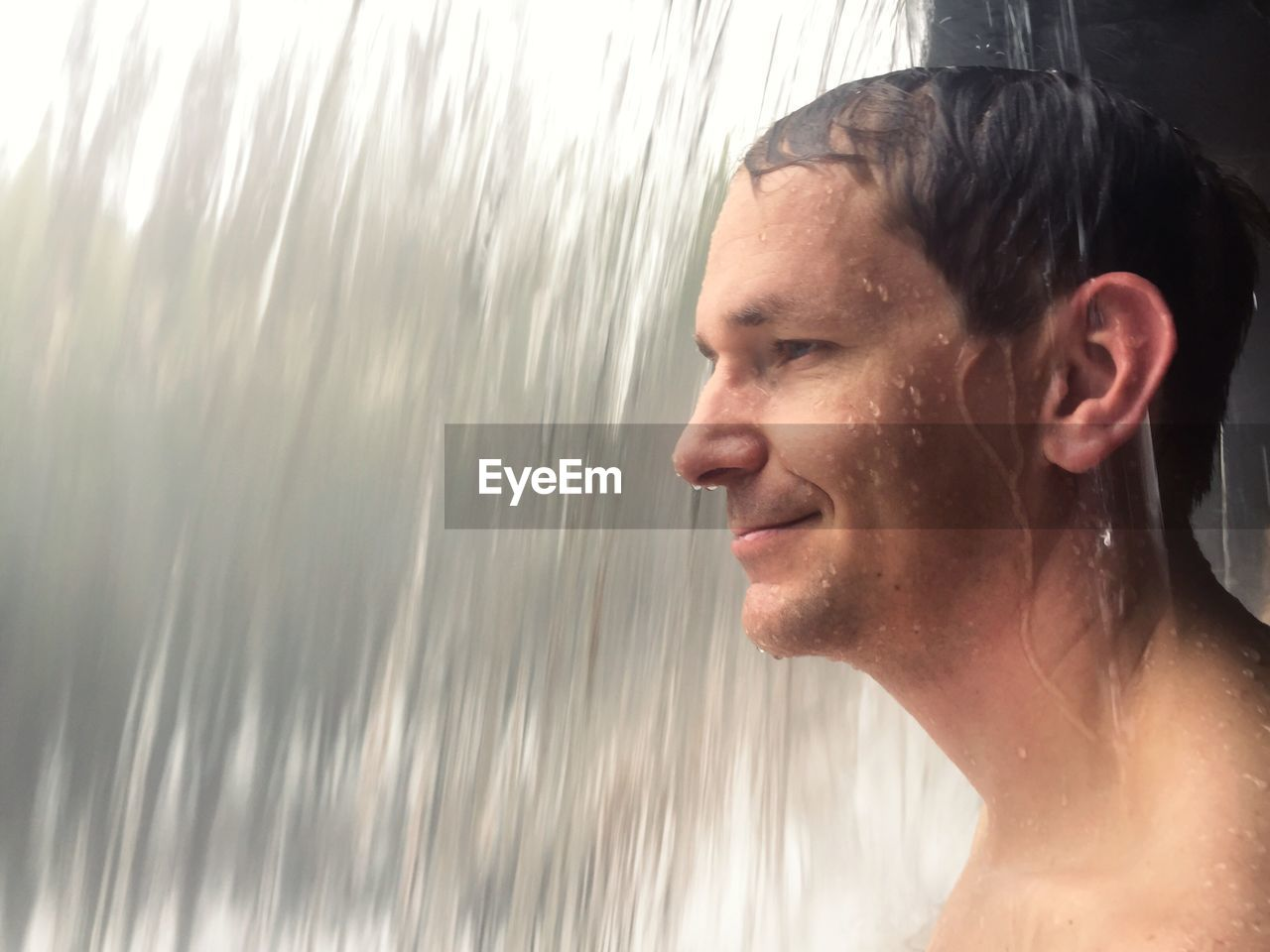 Close-up of smiling mature man bathing in waterfall