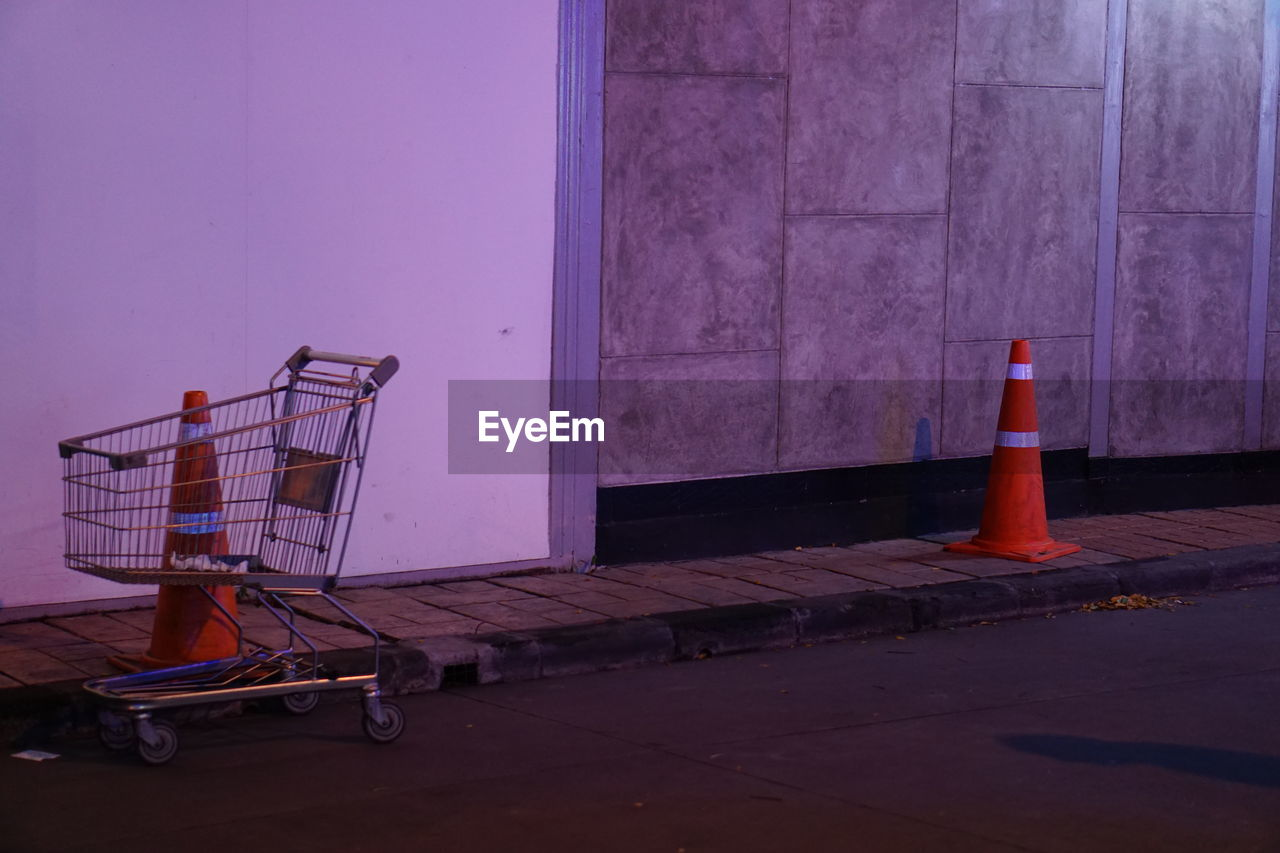 architecture, no people, shopping cart, built structure, safety, cone, outdoors, security, building exterior, transportation, traffic cone, day, shopping, city, wall - building feature, protection, trolley, footpath, orange color, absence, purple, consumerism