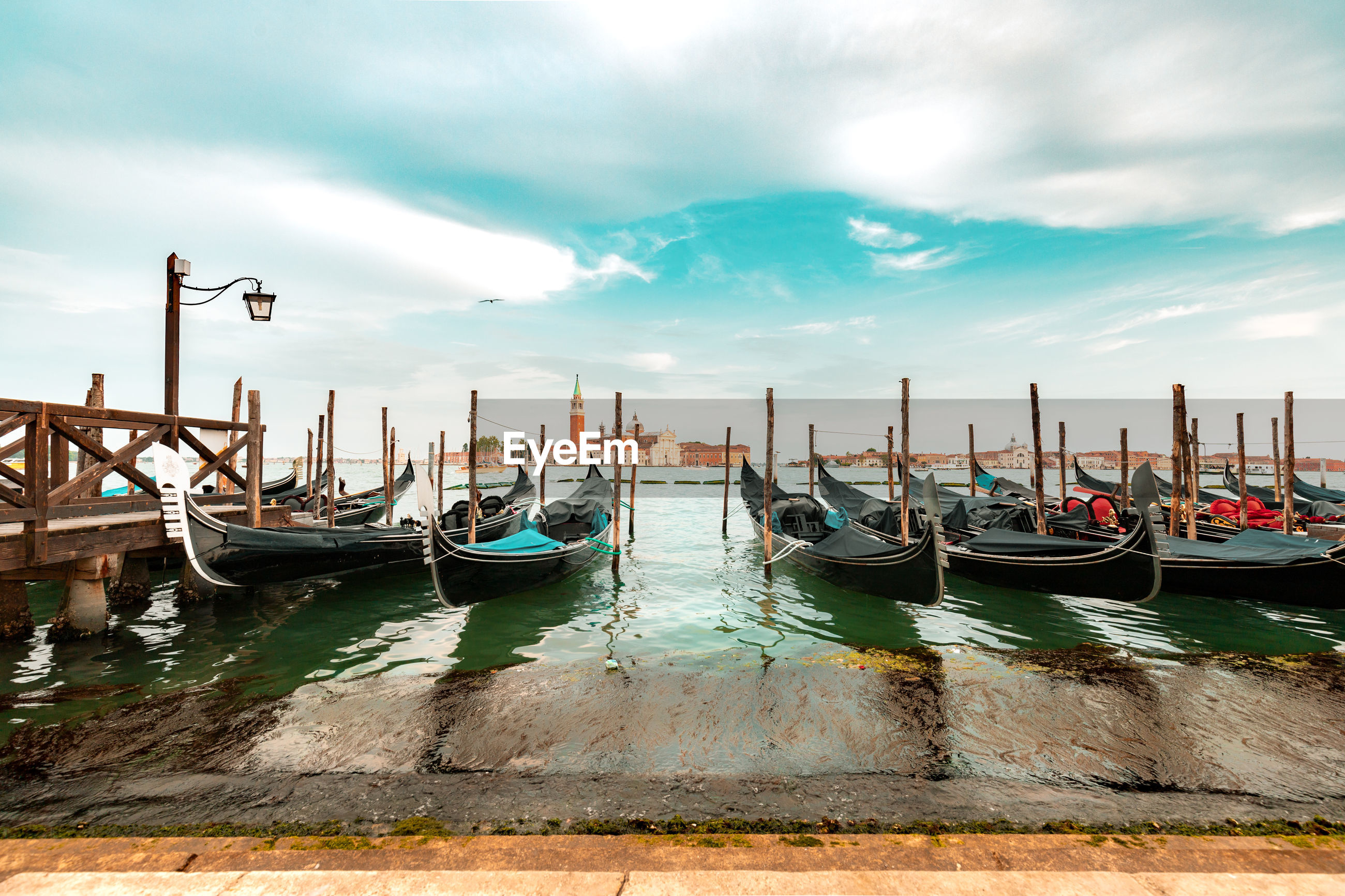 Gondolas moored by wooden posts in canal against sky