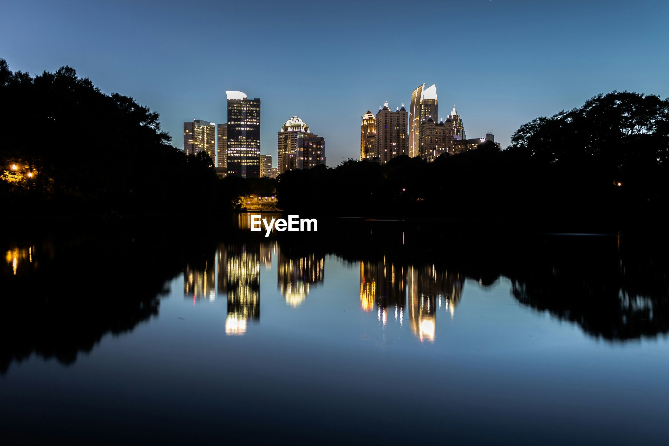 Reflection of skyline in piedmont park lake against clear sky