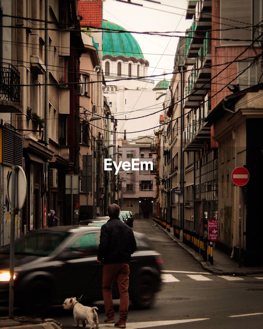 REAR VIEW OF MAN WALKING ON STREET BY BUILDINGS IN CITY