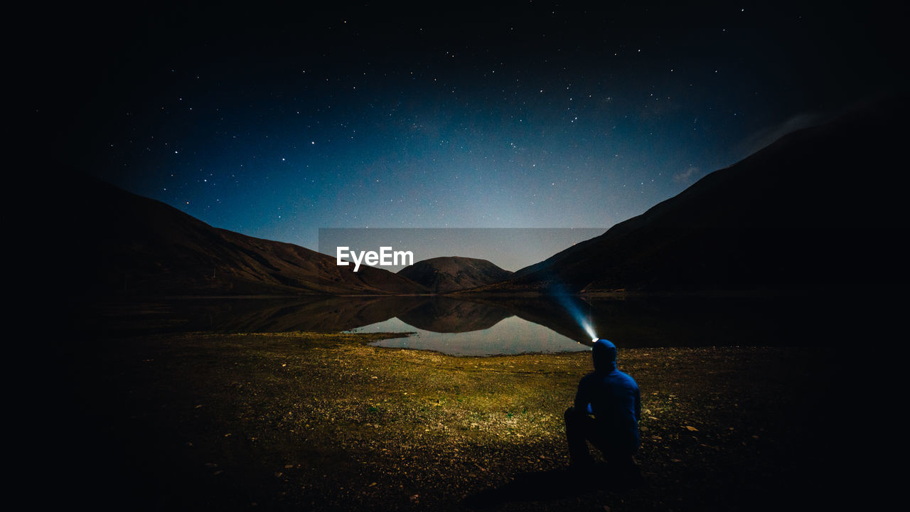 Rear View Of Man With Flashlight Against Star Field At Night