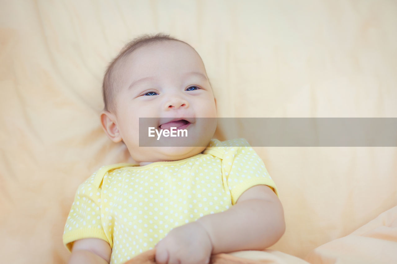 High angle view of cute smiling baby girl lying on bed at home