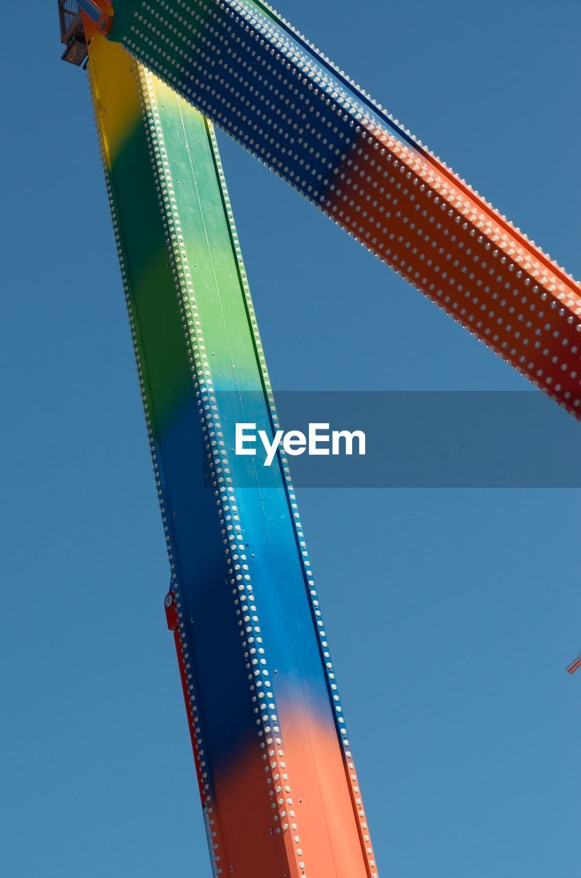clear sky, low angle view, sky, blue, no people, nature, day, multi colored, built structure, architecture, metal, pattern, copy space, red, outdoors, sunlight, close-up, tall - high, decoration, amusement park